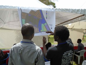 VP of Uganda Society of Architects looking at proposed structure plan.
